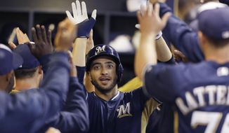 Milwaukee Brewers' Ryan Braun gets high-fives in the dugout after his three-RBI home run against the Kansas City Royals in the third inning of an exhibition baseball game Friday, March 28, 2014, in Milwaukee. (AP Photo/Jeffrey Phelps)