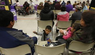 ** FILE ** Eric Alvarez, 4, plays as he and his sister, Emily, 3, wait with their grandparents, Antonio Bello, left, and Maria Refugio, to sign-up for health care coverage at a registration site hosted by Service Employees International Union-United Healthcare Workers, Monday, March 31, 2014, in Sacramento, Calif. (AP Photo/Rich Pedroncelli)