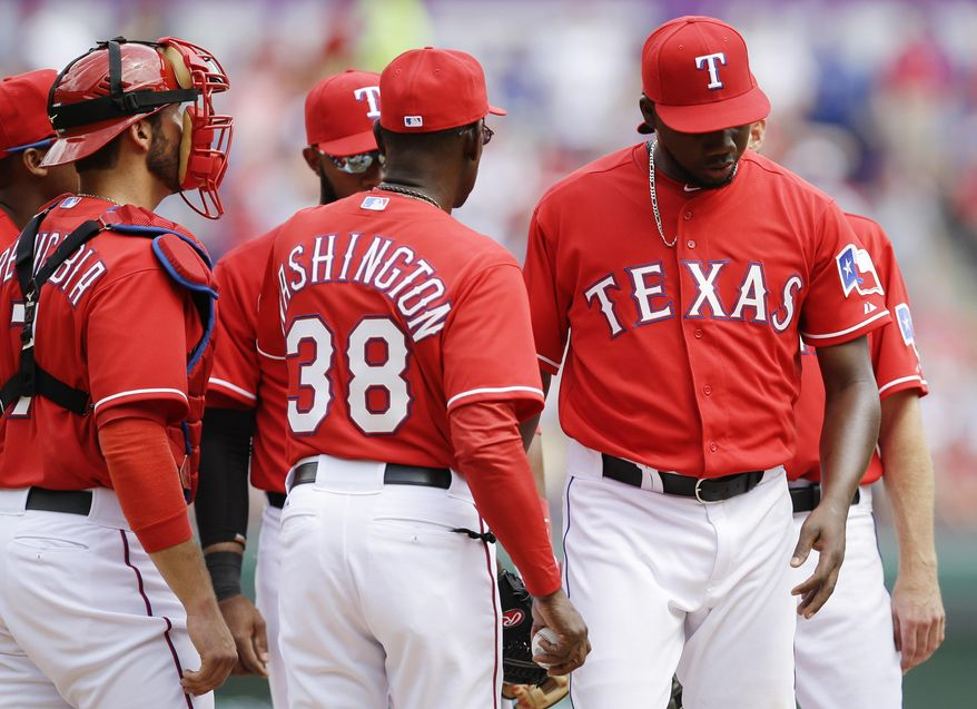 As J.P. Arencibia (7) looks on, Texas Rangers manager Ron Washington (38) takes relief pitcher Pedro Figueroa, right, out of the game during the sixth inning of an opening day baseball game against the Philadelphia Phillies at Globe Life Park, Monday, March 31, 2014, in Arlington, Texas.  (AP Photo/Tony Gutierrez)