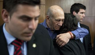 Former Israeli Prime Minister Ehud Olmert hugs a friend before a hearing at Tel Aviv's District Court. Monday, March 31, 2014. The court handed down the verdict in the wide-ranging Jerusalem real estate scandal case related to Olmert's activities before becoming prime minister in 2006. A total of 13 government officials, developers and other businesspeople were charged in three separate schemes. (AP Photo/Dan Balilty, Pool)