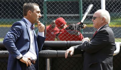 St. Louis Cardinals general manager John Mozeliak, left, talks with Cincinnati Reds general manager Walt Jocketty during batting practice prior to their opening day baseball game, Monday, March 31, 2014, in Cincinnati. (AP Photo/Al Behrman)
