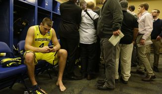 Michigan's Mitch McGary looks at his phone while a teammate is being interviewed in the locker room after an NCAA Midwest Regional final college basketball tournament game against Kentucky Sunday, March 30, 2014, in Indianapolis. Kentucky won 75-72 to advance to the Final Four. (AP Photo/Michael Conroy)