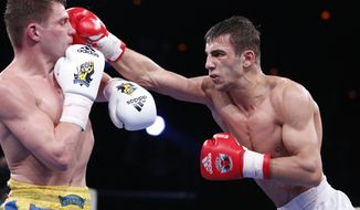 Russia's Radzhab Butaev, right, punches Ukraine's Denis Berinchyk during their light welterweight 64-kg World Series of Boxing quarterfinal bout between Russian Boxing Team and Ukraine Otamans, in Moscow, Russia, Monday, March, 31, 2014. Second leg matches will take part in Donetsk, Ukraine, on April 4. (AP Photo/Denis Tyrin)
