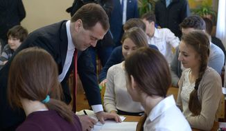 Russian Prime Minister Dmitry Medvedev, second left, speaks to school-children while visiting Crimea in Simferopol, Crimea, Monday, March 31, 2014. Russia's prime minister is visiting Crimea to consider priorities for its economic development following the Russian takeover. Dmitry Medvedev is leading a delegation of Cabinet ministers and is chairing a meeting Monday to discuss priorities for federal assistance to the region, which Russia annexed from Ukraine earlier this month. (AP Photo/RIA-Novosti, Alexander Astafyev, Government Press Service)