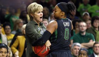 Baylor head coach Kim Mulkey tries grabbing the ball from Baylor guard Odyssey Sims during a stoppage in play against Notre Dame in the second half of their NCAA women's college basketball tournament regional final game at the Purcell Pavilion in South Bend, Ind., Monday, March 31, 2014.   (AP Photo/Paul Sancya)
