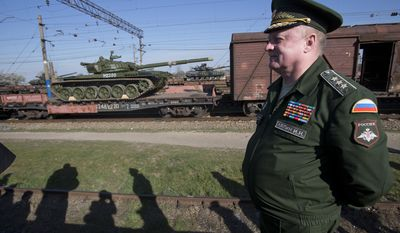 Russian head of Transport Department of the Ministry of Defense Colonel General Igor Lyapin smiles as Russian tanks T-72B, close left, arrive and Ukrainian tanks T-62, center back, are transported to the Ukraine at the Ostryakovo railway station not far from Simferopol, Crimea, Monday, March 31, 2014. (AP Photo/Pavel Golovkin)