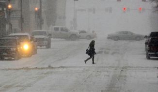 A pedestrian crosses the street in the snow, Monday, March 31, 2014, in Bismarck, N.D. Schools and universities across North Dakota are closing and no travel is advised in many areas because of a spring snow storm on Monday. (AP Photo/The Bismarck Tribune, Tom Stromme)
