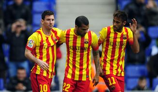 FC Barcelona's Lionel Messi, left, celebrates after scoring a penalty with teammates Neymar, right, and Daniel Alves, center, during a Spanish La Liga soccer match against Espanyol at Cornella-El Prat stadium in Cornella Llobregat, Spain, Saturday, March 29, 2014. (AP Photo/Manu Fernandez)