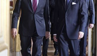 Russian Foreign Minister Sergey Lavrov, left, and French Foreign Minister Laurent Fabius, right, walk along a corridor in the foreign ministry in Paris, Monday, March 31, 2014. Lavrov is in Paris for talks about Ukraine.  (AP Photo/Michel Euler)