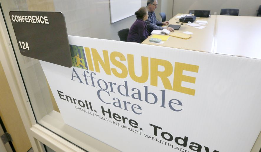 **FILE** A man assists a woman sign up for health insurance at Laman Public Library in North Little Rock, Ark., Monday, March 31, 2014. Monday is the deadline to sign up for private heath insurance in the online markets created by President Obama's heath care law. (AP Photo/Danny Johnston)