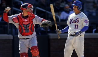 New York Mets' Ruben Tejada, right, reacts after striking out while Washington Nationals catcher Wilson Ramos throws the ball during the seventh inning of the baseball game on Opening Day at Citi Field in New York, Monday, March 31, 2014. The Nationals defeated the Mets in extra innings 9-7. (AP Photo/Seth Wenig)