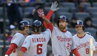 Washington Nationals' Anthony Rendon, second from left, celebrates his three-run home run with teammates Danny Espinosa, right, Adam LaRoche, second from right, and Jose Lobaton during the tenth inning of the baseball game against the New York Mets on Opening Day at Citi Field in New York, Monday, March 31, 2014. The Nationals defeated the Mets in extra innings 9-7. (AP Photo/Seth Wenig)