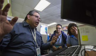 ** FILE ** Staffer Thomas Sundoval, left, assists Jaime Sanchez, center, 50, and his wife Carmen Castro, right, 50, during a health care enrollment event at AltaMed Health Insurance Resource Center, Monday, March 31, 2014, in Los Angeles. (AP Photo/Ringo H.W. Chiu)