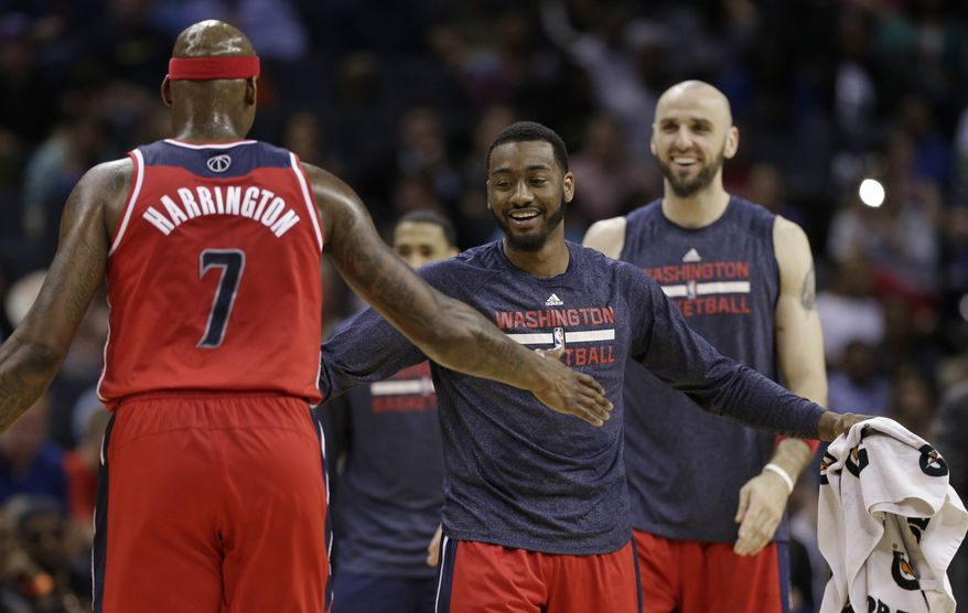 Washington Wizards' John Wall, right, congratulates Al Harrington, left, during a timeout in the first half of an NBA basketball game against the Charlotte Bobcats in Charlotte, N.C., Monday, March 31, 2014. (AP Photo/Chuck Burton)