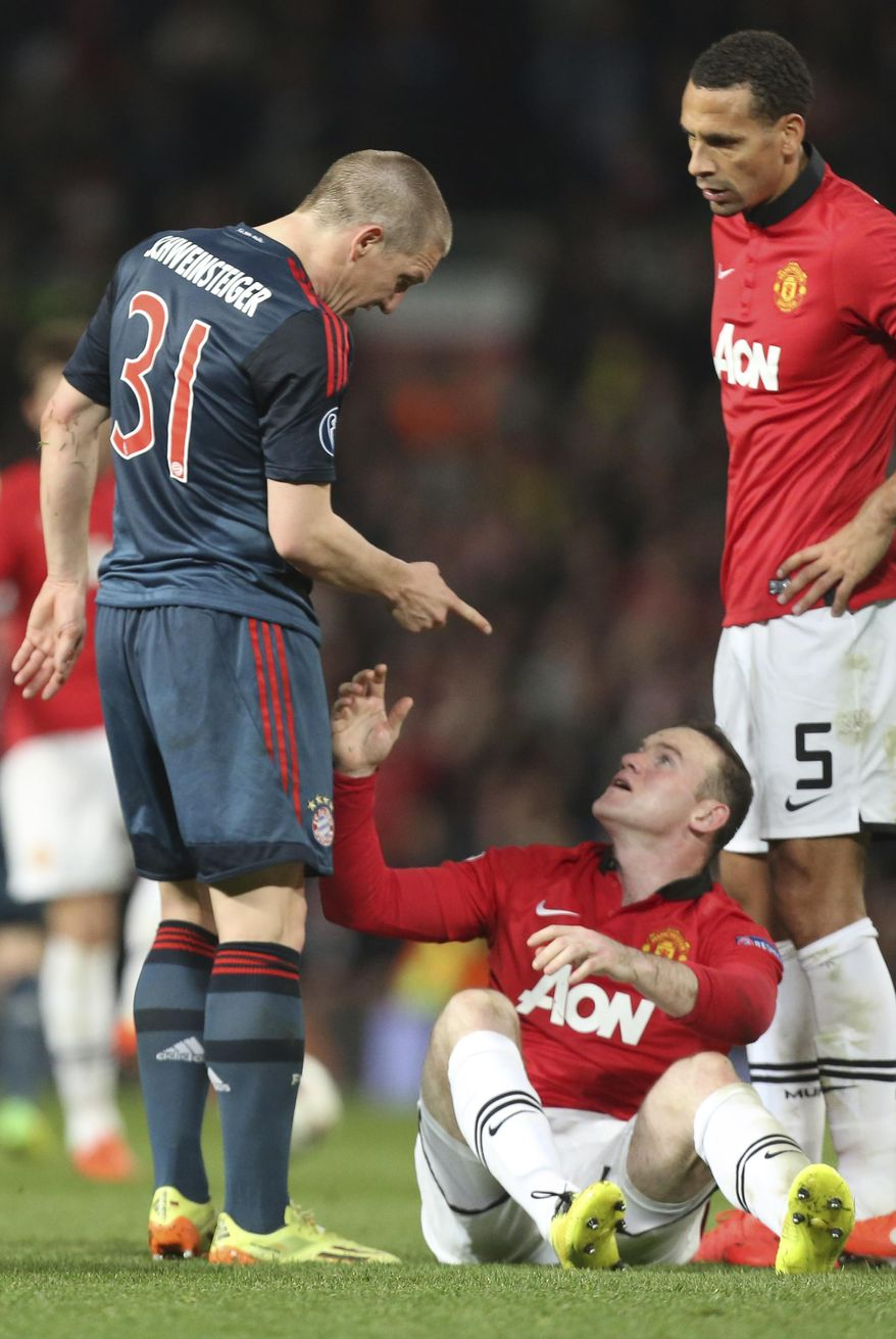 Bayern's Bastian Schweinsteiger, left, argues with Manchester United's Wayne Rooney, bottom, after he was sent off the field during the Champions League quarterfinal first leg soccer match between Manchester United and Bayern Munich at Old Trafford Stadium, Manchester, England, Tuesday, April 1, 2014.(AP Photo/Jon Super)
