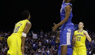 Michigan's Nik Stauskas (11) and Derrick Walton Jr. (10) watch as Kentucky's Dakari Johnson dunks during the second half of an NCAA Midwest Regional final college basketball tournament game Sunday, March 30, 2014, in Indianapolis. (AP Photo/David J. Phillip)