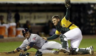 Cleveland Indians' Michael Brantley, left, is tagged out by Oakland Athletics catcher John Jaso in the sixth inning of a baseball game Monday, March 31, 2014, in Oakland, Calif. Brantley was attempting to score on a hit by Cleveland Indians' Ryan Raburn. (AP Photo/Ben Margot)