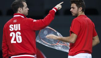 Swiss Davis Cup Team captain Severin Luethi, left, speaks  to Stanislas Wawrinka, right, of Switzerland, during a training session of the Swiss Davis Cup team prior to the tennis Davis Cup world group quarterfinal match between Switzerland and Kazakhstan,   in Geneva, Switzerland, Tuesday, April 1, 2014. (AP Photo/Keystone,Salvatore Di Nolfi)