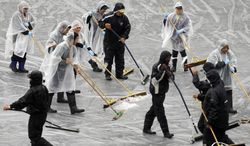 Workers clear water off a tarp covering the infield prior to a baseball game between the Cleveland Indians and the Oakland Athletics on Tuesday, April 1, 2014, in Oakland, Calif. (AP Photo/Ben Margot)