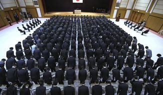 New ministry workers bow during a welcome ceremony for them at Defense Ministry in Tokyo, Tuesday, April 1, 2014. Japan relaxed a decades-old ban on military-related exports Tuesday in a bid to expand joint arms development with allies and equipment sales to Southeast Asia and elsewhere. (AP Photo/Eugene Hoshiko)