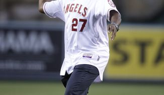 Vladimir Guerrero throws the ceremonial first pitch before an opening day baseball game between the Los Angeles Angels and the Seattle Mariners on Monday, March 31, 2014, in Anaheim, Calif. Guerrero signed a one-day contract to retire with the Los Angeles Angels on Monday. (AP Photo/Jae C. Hong)