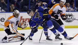 St. Louis Blues' T.J. Oshie (74) falls backward while trying to reach a puck as teammate David Backes stands by along with Philadelphia Flyers goalie Ray Emery (29) and Andrew MacDonald (47) during the second period of an NHL hockey game Tuesday, April 1, 2014, in St. Louis. (AP Photo/Jeff Roberson)