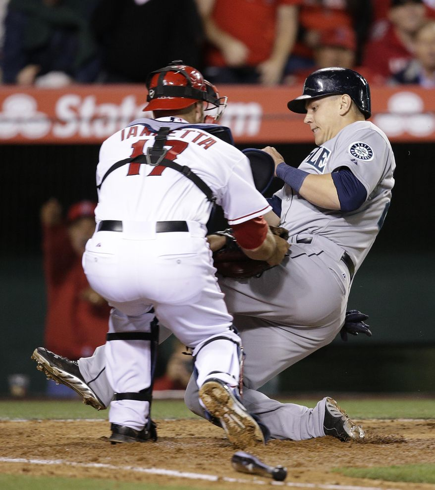 Seattle Mariners' Logan Morrison, right, is tagged out by Los Angeles Angels catcher Chris Iannetta as Morrison tries to score on a double hit by by Kyle Seager during the sixth inning of a baseball game on Monday, March 31, 2014, in Anaheim, Calif. (AP Photo/Jae C. Hong)