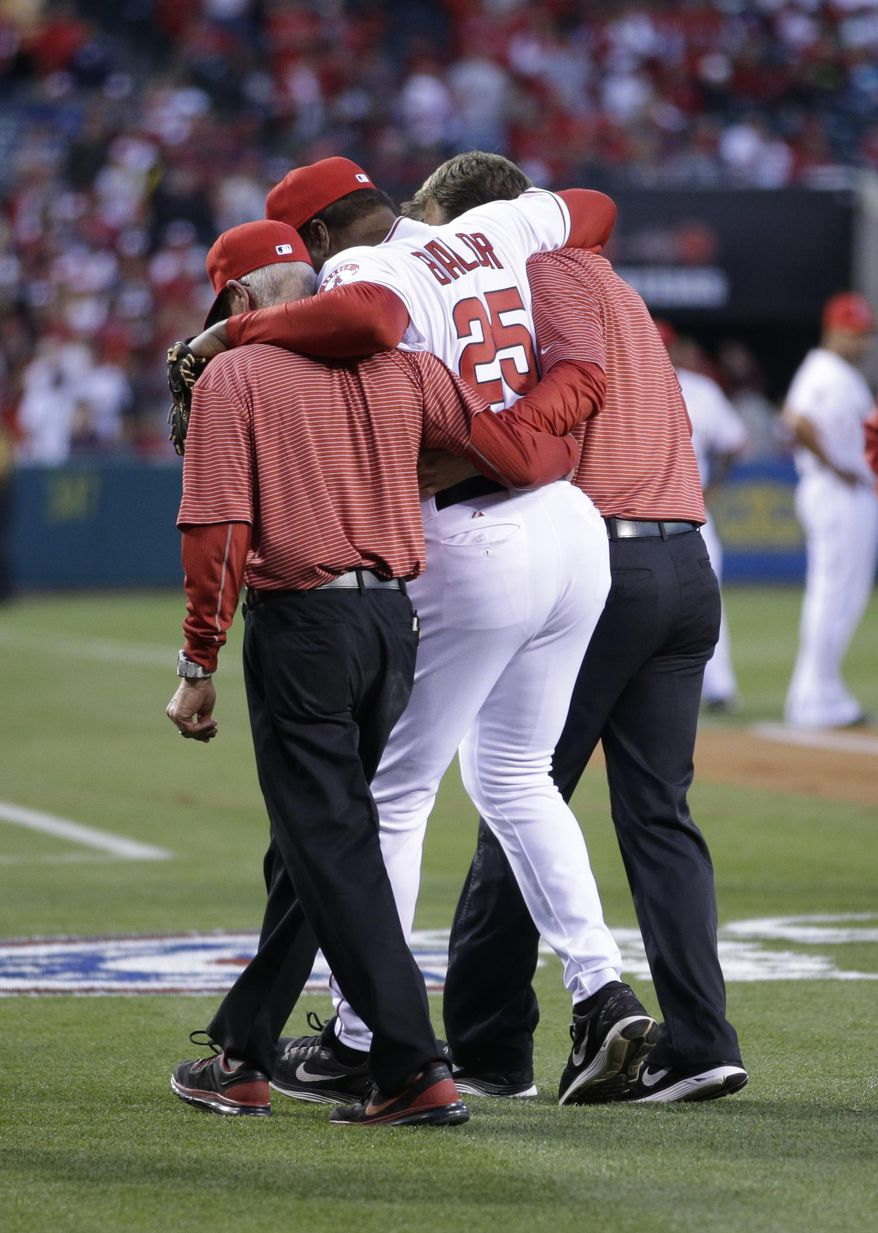 In this March 31, 2014 photo, Los Angeles Angels hitting coach Don Baylor is helped off the field after he broke his right leg while catching Vladimir Guerrero's ceremonial first pitch before the Angels' opening day baseball game with the Seattle Mariners, in Anaheim, Calif. (AP Photo/Jae C. Hong)