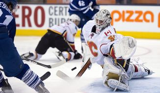 Calgary Flames goaltender Karri Ramo makes a save on Toronto Maple Leafs right winger Phil Kessel during second period NHL action in Toronto on Tuesday April 1, 2014.  (AP Photo/The Canadian Press, Frank Gunn)