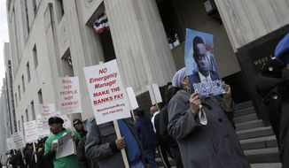 Protestors, against deeper cuts in pensions, march in front of the Theodore Levin Federal Courthouse in Detroit, Tuesday Apr. 1, 2014. Detroit's updated bankruptcy plan was filed in federal court on Monday, revealing new details on how the city plans to restructure its debt and provide public services during the largest municipal bankruptcy in U.S. history. (AP Photo/Detroit Free Press, Mandi Wright)  DETROIT NEWS OUT;  NO SALES