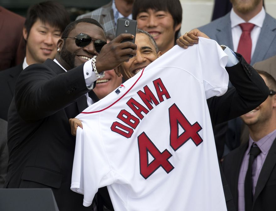 """Boston Red Sox player David """"Big Papi"""" Ortiz takes a selfie with President Barack Obama, holding a Boston Red Sox jersey presented to the president during a ceremony on the South Lawn of the White House in Washington, Tuesday, April 1, 2014, where the president honored the 2013 World Series baseball champion Boston Red Sox. In the background are pitchers Junichi Tazawa, left, Koji Uehara, right.  (AP Photo/Carolyn Kaster)"""