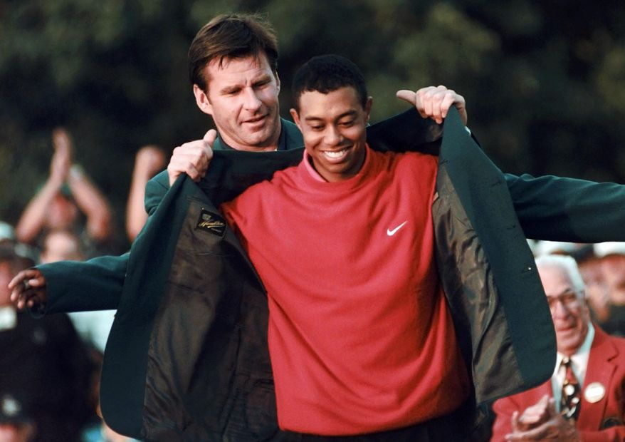 FILE - In this April 13, 1997, file photo, Masters champion Tiger Woods receives his green jacket from the previous year's winner Nick Faldo, rear, at the Augusta National Golf Club in Augusta, Ga. Woods will miss the Masters for the first time in his career after having surgery on his back. Woods said on his website that he had surgery Monday, March 31, 2014, in Utah for a pinched nerve that had been hurting him for several months. (AP Photo/Dave Martin, File)