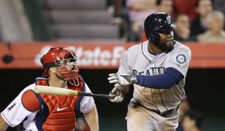 Seattle Mariners' Abraham Almonte, right, watches his RBI double during the seventh inning of a baseball game against the Los Angeles Angels on Monday, March 31, 2014, in Anaheim, Calif. (AP Photo/Jae C. Hong)
