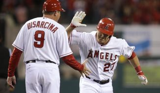 Los Angeles Angels' Mike Trout, right, celebrates his two-run home run with third base coach Gary DiSarcina during the first inning of a baseball game against the Seattle Mariners on Monday, March 31, 2014, in Anaheim, Calif. (AP Photo/Jae C. Hong)