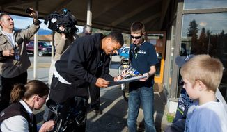 Seattle Seahawks linebacker Malcolm Smith, center, signs autographs outside the Darrington Community Center on Monday, March 31, 2014, in Darrington, Wash. Twelve players from the NFL football team and the Seattle Sounders MLS soccer team visited Darrington to lend support to the town which is located near the site of the  March 22, massive mudslide that hit the community of Oso, Wash. (AP Photo/The Seattle Times, Marcus Yam, Pool)