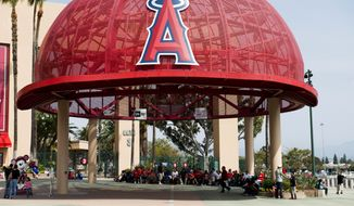 Fans wait under a large Los Angeles Angels hat structure prior to the game between the Los Angeles Angels and Los Angeles Dodgers of a spring exhibition baseball game in Anaheim, Calif., Saturday, March 29, 2014. (Associated Press)
