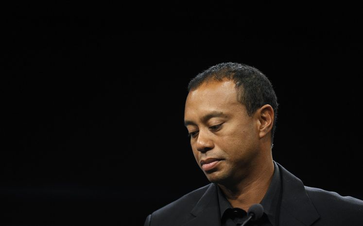 FILE - In this March 24, 2014, file photo, Tiger Woods looks down during a news conference at the Newseum in Washington, Monday, March 24, 2014. Woods will miss the Masters for the first time in his career after having surgery on his back. Woods said on his website that he had surgery Monday, March 31, in Utah for a pinched nerve that had been hurting him for several months. (AP Photo/Susan Walsh, File)