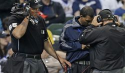 Umpire Ted Barrett (65) listens to a headset during instant replay in the sixth inning of an Opening day baseball game between the Atlanta Braves and Miwaukee Brewers Monday, March 31, 2014, in Milwaukee. Atlanta got a reversal of a call against the Milwaukee Brewers Ryan Braun at first base. (AP Photo/Jeffrey Phelps)