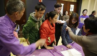 ** FILE ** In this photo taken Monday, March 31, 2014, applicants are given instructions how to check in for a health care enrollment event at the Oakland Asian Cultural Center in Oakland, Calif. (AP Photo/Eric Risberg)
