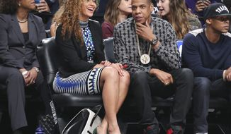 Recording artists Beyonce, center left, and Jay-Z, attend a NBA basketball game between the Brooklyn Nets and Houston Rockets at the Barclays Center, Tuesday, April 1, 2014, in New York. (AP Photo/John Minchillo)