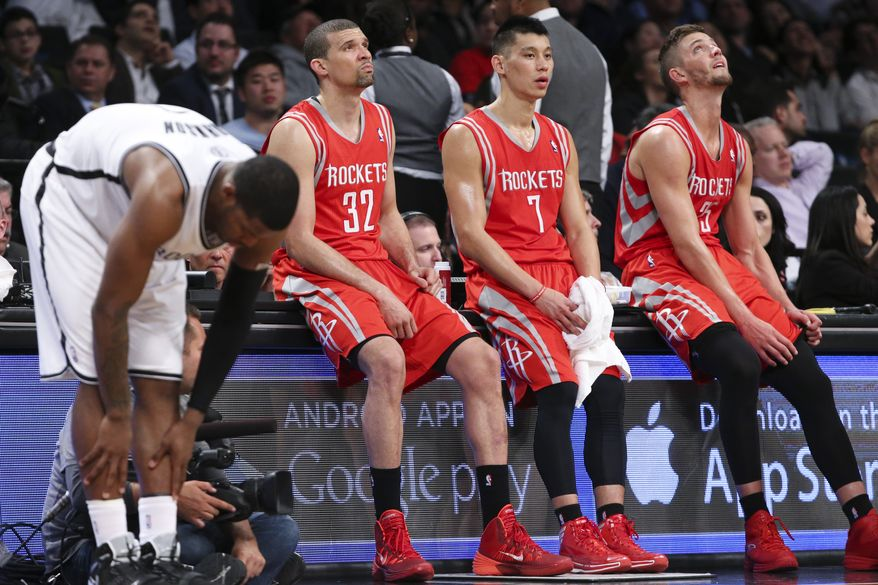 Houston Rockets guard Francisco Garcia (32), guard Jeremy Lin (7), and forward Chandler Parsons (25) sit on the scorers table as they wait for play to resume during the second half of their NBA basketball game against the Brooklyn Nets at the Barclays Center, Tuesday, April 1, 2014, in New York. (AP Photo/John Minchillo)