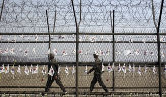 South Korean soldiers patrol through the military wire fences with hanging national flags at the Imjingak Pavilion near the border village of Panmunjom, which has separated the two Koreas since the Korean War, in Paju, north of Seoul, Tuesday, April 1, 2014. North and South Korea fired hundreds of artillery shells into each other's waters Monday in a flare-up of animosity that forced residents of five front-line South Korean islands to evacuate to shelters for several hours, South Korean officials said. (AP Photo/Lee Jin-man)