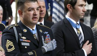 Medal of Honor recipients Sgt. 1st Class Leroy Petry, left and Capt. William Swenson, right, stand during the Pledge of Allegiance, Wednesday, April 2, 2014, at the Capitol in Olympia, Wash., during a ceremony to honor them and other recipients  of the Medal of Honor who are from Washington state. Petry lost his hand in 2008 when an enemy grenade he was throwing away from fellow soldiers detonated while in combat in Afghanistan. (AP Photo/Ted S. Warren)