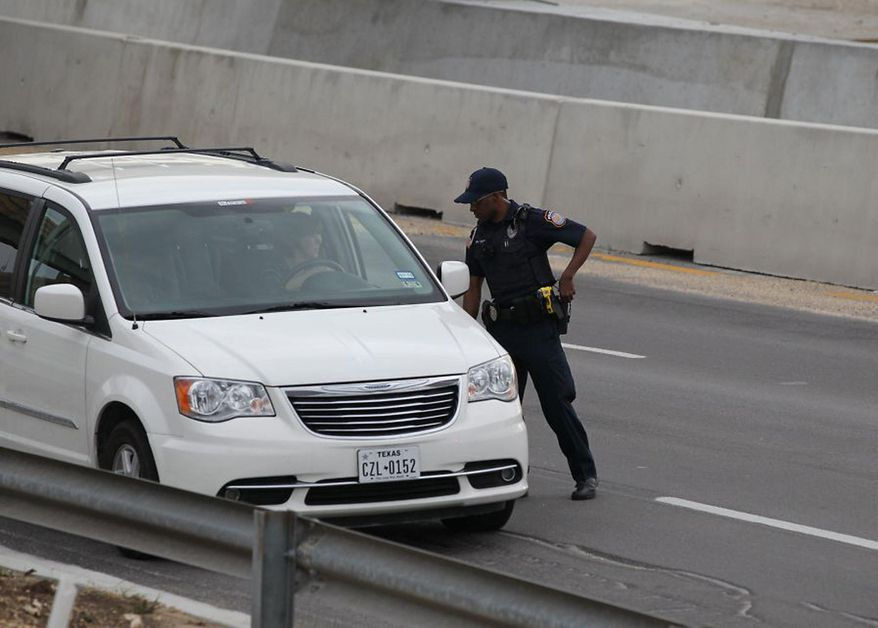 A police officer checks drivers' IDs outside the main gate at Fort Hood, Texas, after a shooting at the Army base Wednesday, April 2, 2014.  One person was killed and at least 14 injured in a shooting Wednesday at Fort Hood. (AP Photo/Austin American-Statesman, Deborah Cannon)  AUSTIN CHRONICLE OUT, COMMUNITY IMPACT OUT, MAGS OUT; NO SALES; INTERNET AND TV MUST CREDIT PHOTOGRAPHER AND STATESMAN.COM