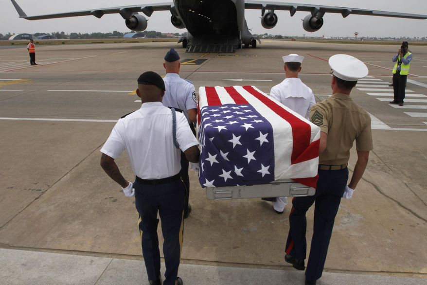 ** FILE ** Four U.S. servicemen carry a coffin draped with the U.S. flag containing possible remains of a U.S. serviceman to a C-17 cargo plane during a repatriation ceremony at Phnom Penh International Airport, Cambodia, Wednesday, April 2, 2014. The possible remains of U.S. soldiers found in eastern Kampong Cham province were repatriated to Hawaii for testing. (AP Photo/Heng Sinith)
