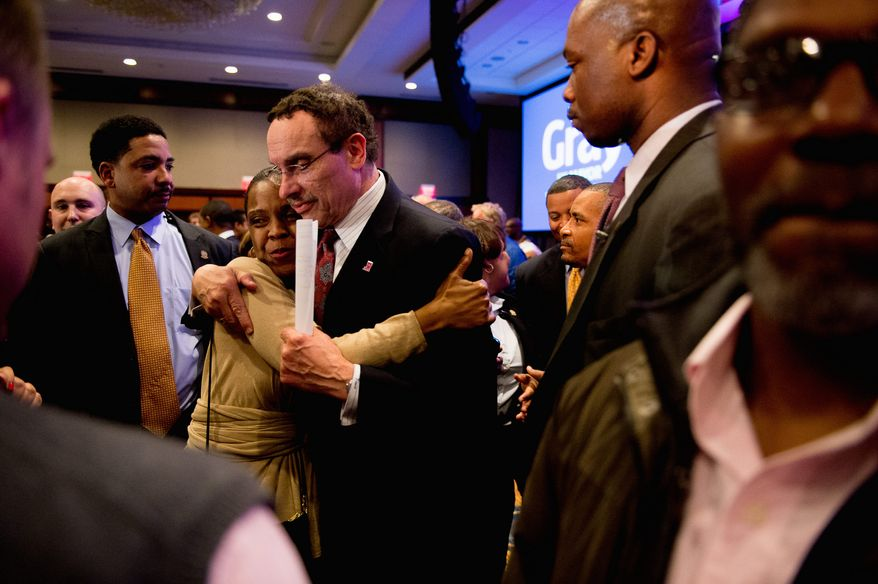 D.C. Mayor Vincent C. Gray hugs a supporter after delivering his concession speech Tuesday night after losing the Democratic primary to Muriel Bowser. (Andrew Harnik/The Washington Times)