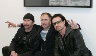 ** FILE ** This Oct. 9, 2005, file photo shows U2's Bono, right, and guitarist The Edge, left, posing with photographer Anton Corbijn in New York, under a portrait of the band from the Joshua Tree album cover. The Library of Congress announces the sound recordings it has selected for long-term preservation in the National Recording Registry Wednesday, April 2, 2014. (AP Photo/Diane Bondareff, File)