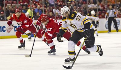 Boston Bruins forward Patrice Bergeron (37) skates with the puck while pursued by Detroit Red Wings defenseman Kyle Quincey (27) and forward Joakim Andersson (63), during the first period of an NHL hockey game in Detroit, Mich., Wednesday, April 2, 2014. (AP Photo/Tony Ding)