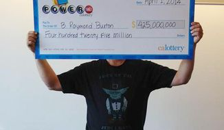 """This photo provided by the California Lottery shows Powerball winner B. Raymond Buxton holding a check for $425 million, Tuesday, April 1, 2014, in Sacramento, Calif. The sole winner of February's $425 million Powerball jackpot came forward to claim his prize Tuesday. Buxton was wearing a shirt that featured a picture of Yoda and read, """"Luck of the Jedi I have,"""" according to lottery officials. The one winning ticket for the Feb. 19 drawing was sold at a convenience store in Milpitas, Calif., north of San Jose. (AP Photo/California Lottery)"""