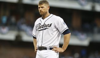 San Diego Padres' Chase Headley stands at first base awaiting his glove after grounding into a double play to end a Padres' threat in the eighth inning of baseball game against the Los Angeles Dodgers Tuesday, April 1, 2014, in San Diego. It was second time Headley grounded into a double to end an inning.  (AP Photo/Lenny Ignelzi)